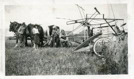 A Group of People With A Horse Drawn Combine