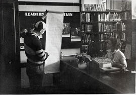 M.R. Murray helps a student at the library desk
