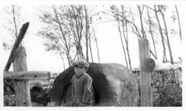 Boy seated on an outdoor clay oven