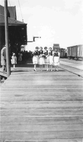 Five Girls on a train platform.